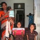 bambina sostenuta con mamma e sorelle