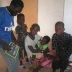 volontario senegalese con alcuni bambini sostenuti